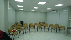 Classroom ready for use, white walls, chairs in rows,